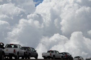 Clouds moving up fast by the parked vehicles